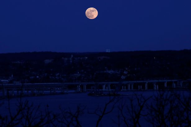 A supermoon full moon is seen above the Hudson River and the Mario M Cuomo Bridge from Nyac